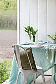 Pastel tablecloth, vases of lily of the valley and place settings on table next to chair with cushion