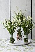Posies of lily of the valley on white plate