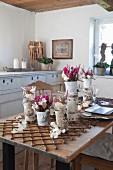 Mit Naturmaterialien dekorierte Vasen und Blumengestecke auf rustikalem Tisch in bäuerlichem Esszimmer