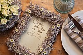 Hand-written message with frame decorated with waxflowers and grape stems painted white