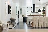 Essplatz mit geschnürten Hussenstühlen in offener Küche mit schwarzer Abzugshaube über Theke