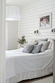 Scatter cushions on double bed in bedroom with wooden wall