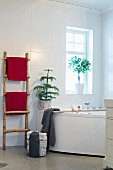 Rustic ladder used as towel rack and small conifer on edge of whirlpool bathtub as festive decoration