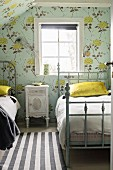 Vintage-style bedroom with floral wallpaper and bedside cabinet between twin metal beds with frames painted grey below window
