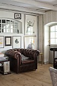 Brauner Ledersessel vor Wand mit Bildersammlung in rustikal ländlichem Zimmer