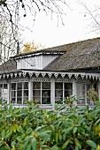 Blick vom Garten auf Wohnhaus mit Anbau, an Fenster und Traufkante befestigtes Zierbrett grau lackiert