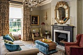 Classic living room with various upholstered furnishings in front of fireplace and impressive mirror
