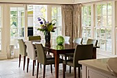 Dining area in conservatory with lattice windows, wooden table and upholstered chairs with various covers