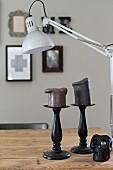Dark pillar candles on black candlesticks below desk lamp on wooden table