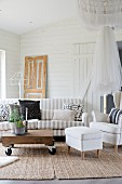 White armchair and footstool and striped sofa around wooden table on castors in living room with white wood cladding