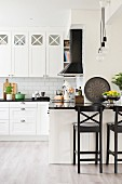 Black bar stools at counter in white country-house kitchen