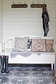 Scatter cushions on white-painted wooden bench below coat racks on white wooden wall and retro-patterned wall tiles