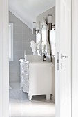 Bright bathroom; vintage chest of drawers painted white with modern countertop basin below carved mirror and stainless steel sconce lamps