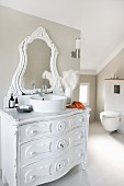 Modern bathroom with sloping ceiling and wall-mounted toilet; vintage chest of drawers painted white with round, modern countertop washbasin and carved mirror