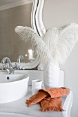 White ostrich feathers in elegant porcelain vase on vintage washstand with vanity mirror