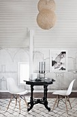 Classic chairs with white shell seats at black, vintage-style table below spherical pendant lamps suspended from ceiling