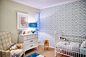 White cot against retro wallpaper and patterned armchair next to white chest of drawers