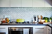 White kitchen with L-shaped counter, gas hob and splashback with fish-scale pattern