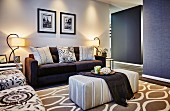 Ottoman in front of dark sofa with various scatter cushions in brightly lit, elegant living room in mixture of patterns