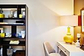 Tischleuchte mit gelbem Keramik Lampenfuss auf beleuchtetem, zierlichem Schreibtisch, seitlich dunkles Regal mit Vasensammlung