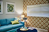 Cups on tray on blue, velvet, round ottoman and pale blue sofa in living room; ornately patterned wallpaper on accent wall and closed louvre blind on window