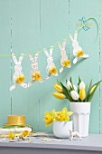 Easter arrangement in pastel shades; garland of paper bunnies, vases of narcissus and tulips