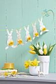 Osterdeko in Pastellfarben: Hasen-Girlande aus Papier mit Narzissen und Tulpenstrauss