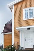 Elegantes Haus mit Holzverschalung und weißem, überdachtem Eingang