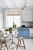 weiße, skandinavische Landhausküche mit hellblauem Gasherd, Polstersessel, Tisch und Holzhocker mit nostalgischem Flair