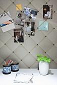 Elegante, gepolsterte Pinnwand mit eingesteckten Postkarten, davor weiße Schreibtischplatte mit Stiftehalter und Blumenvase