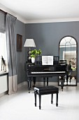 Black piano and stool on white wooden floor