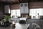 View across dining table of kitchen counter with grey-painted wooden doors in rustic wooden house