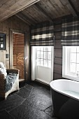 Bathroom with black slate floor, lattice windows, tartan roller blinds and view into sauna in background