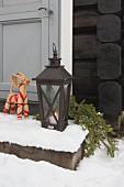 Straw animal figurine next to lit candle in floor lantern on snowy step