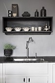 Kitchen counter with integrated sink and modern tap fitting below shelving unit mounted on grey-painted wall