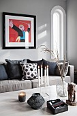 Lit candles in candelabra and tealight holder on table, scatter cushions on sofa below modern artwork on grey wall in traditional interior