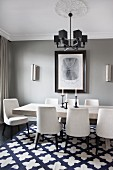 White-upholstered chairs around table with wooden top on patterned rug below pendant lamp with black cubic lampshades