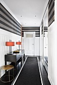 Black runner, table lamps on console table and white wainscoting below grey striped walls in elegant hallway