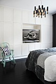 Bed with patchwork bedspread opposite white fitted wardrobes with flatscreen TV in niche