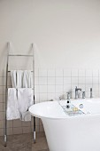 Free-standing bathtub next to stainless steel ladder-style towel rack