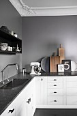 L-shaped kitchen counter with dark stone counter and white base units below grey wall and stucco ceiling