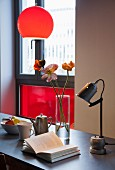 Vintage metal table lamp and open book below pendant lamp with red spherical lampshade