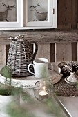 Thermos jug with wicker cover and coffee cup on white chip wood tray on festively decorated table
