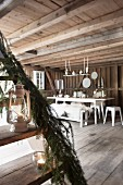 Staircase decorated with fir branches and tealight holders in front of dining area in rustic wooden house