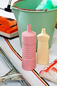 Pastel cleaning agent bottles, bucket and retro carpet sweeper on woven rug