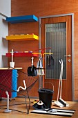 Cleaning utensils and retro wire armchair in front of brightly coloured shelved on wood-clad wall