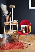 Cleaning brushes with wooden handles and feather duster on step stool; metal bucket on non-slip mat and children's book on red chair
