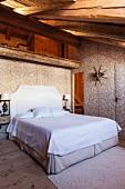 Floral gemusterte elegante Textilbespannung in Schlafraum unterm Dach mit Doppelbett in restauriertem Chalet