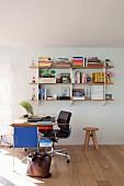 Klassiker Bürostuhl mit schwarzem Lederbezug und moderner Schreibtisch vor Wandregal
