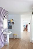 Standwaschbecken und Spiegel an tapezierter Wand mit Retro Muster in offenem Raum, Blick durch mehrere Durchgänge auf Frau im Hintergrund